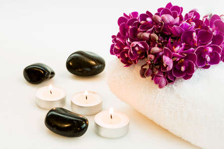 bouquet of purple orchids, candles and stones on a white towel isolated on a white background