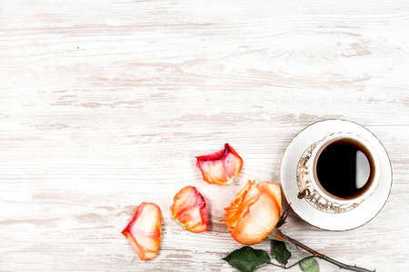A cup of coffee, and an orange rose and petals on a background of vintage boards Stock fotó
