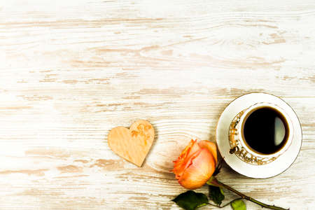 A cup of coffee, and an orange rose and heart on a background of vintage boards Stock fotó