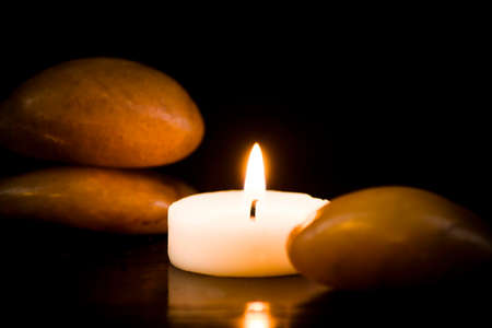 Bright stones and lit candle on a dark background