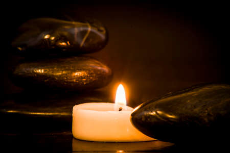 Dark stones and lit candle on a dark background Stock fotó