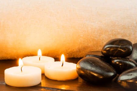 Dark stones and lit candles against a white towel