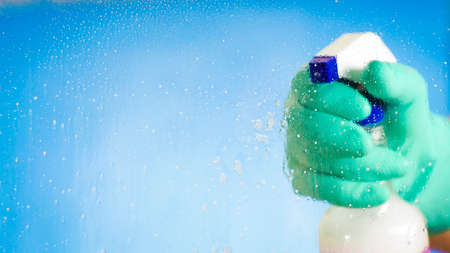 Hand in green glove holding a washer - washing the glass on a blue background Stockfoto