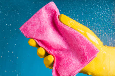 Hand in yellow glove holding a dishcloth - washing the glass on a blue background