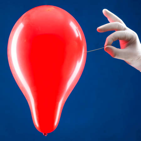 Hand in white glove piercing a red balloon Banco de Imagens