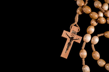 A bright brown rosary lying on a black background