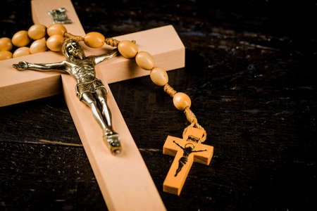 Light brown wooden cross on old boards with a rosary