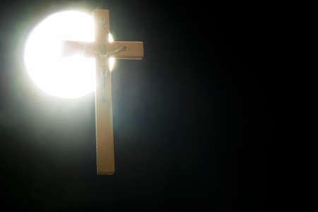 A crucifix against a round white light, against a black background 免版税图像