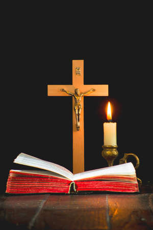 Book on the background of a crucifix, and a lit candle in a candlestick on a black background