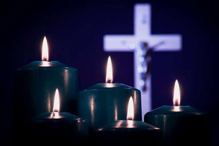 Velas encendidas en una cruz blanca, sobre un fondo azul. Foto de archivo