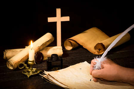 A hand writing with a pen on the background of papyrus scrolls, against the background of a candle and a cross, against a dark background Banco de Imagens