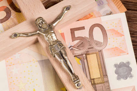 Crucifix with a cross on euro banknotes
