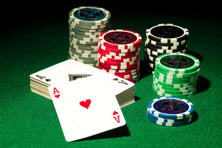 Gambling concept - playing cards and chips on a green gown Stock Photo