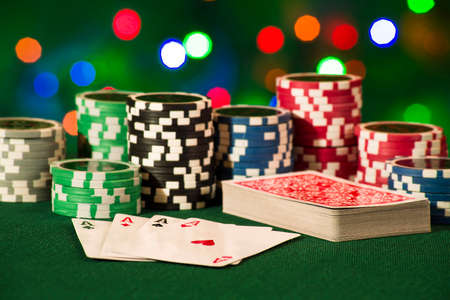 Gambling concept - cards and chips on green dresses on bokeh lights background Stock Photo