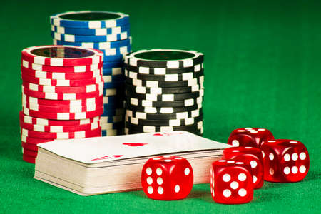Gambling concept - cards, bones and chips on a green gown