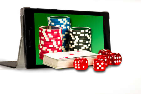 The concept of online gambling, dice, chips, and cards on a background of a tablet with a green background Stock Photo