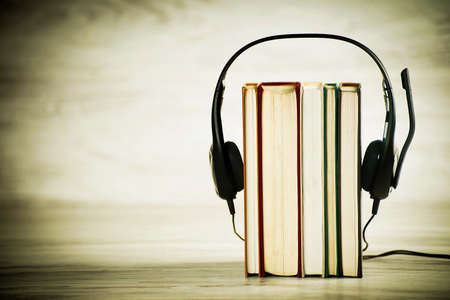 Concept of audiobooks, headphones with microphone and books on vintage background Reklamní fotografie