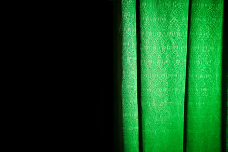 Half-exposed green curtain on a black background