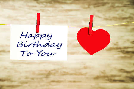 A card and a red heart hanging on a string, fastened with red buckles with the words Happy Birthday