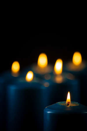 Lit blue candles isolated on a black background