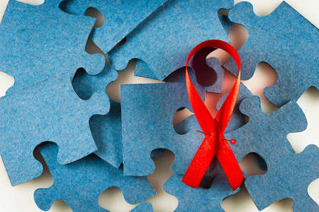 Un ruban rouge contre un puzzle bleu