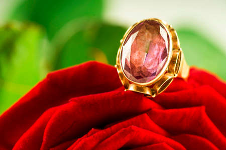 Gold ring with sapphire on a red rose background