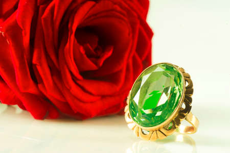 Gold ring with sapphire on a red rose background Reklamní fotografie