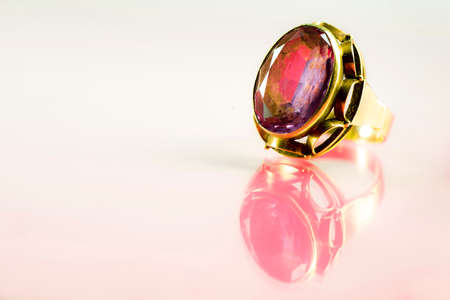 A ring in a golden frame with a colored stone on a bright crimson background