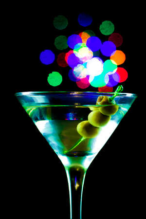 A martini glass with olives isolated on a black background 免版税图像