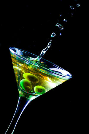 A martini glass with olives isolated on a black background Stockfoto