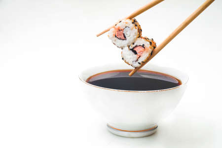 Sushi held in chopsticks over a bowl with sauce isolated on a white background Imagens