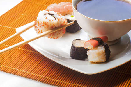 Sushi held in chopsticks over a bowl with sauce isolated on a white background Stockfoto