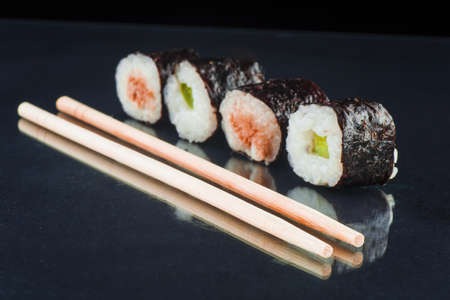 Sushi and chopsticks isolated on a black glass background Imagens