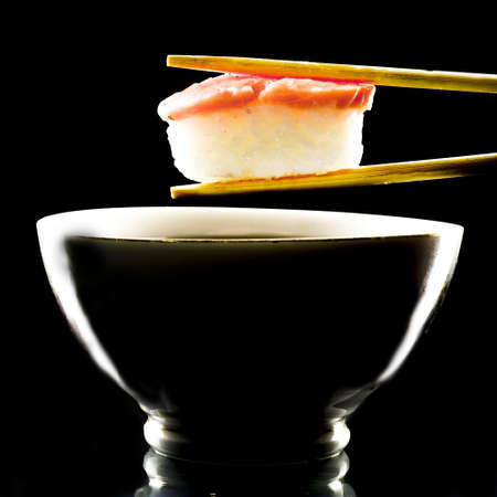 Sushi held in chopsticks over a bowl with sauce isolated on a black background
