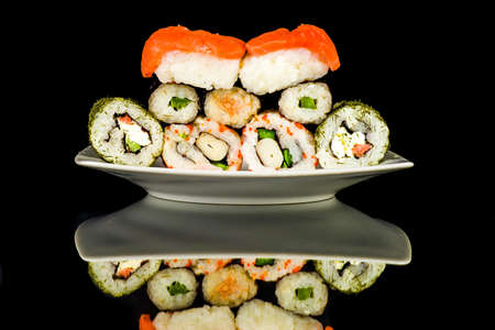 Sushi spread out on a plate isolated on a black background