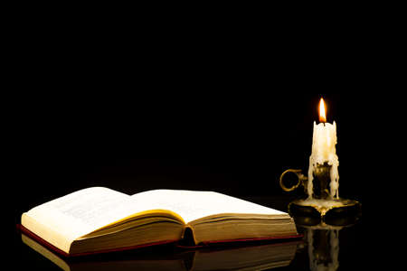 An open book with a lit candle on a black background