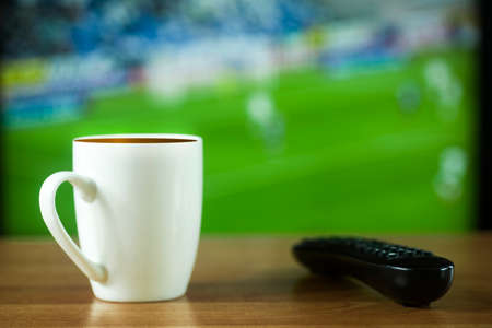 Mug with coffee and TV remote control on the background of the TV screen with a view of the match