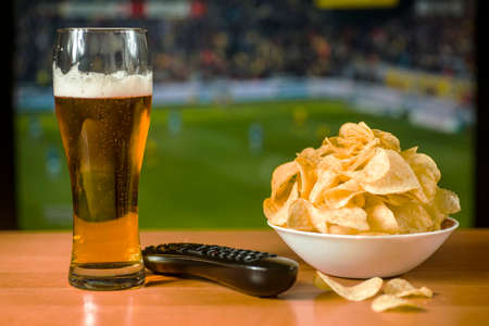 A glass of beer, a bowl of crisps and a TV remote on the TV screen with a view of the match Stockfoto