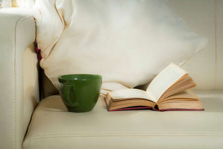A green mug and a book, on a background of pillows on a light bed Stockfoto