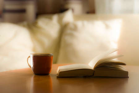 A glass of tea and a book on the table, on the background of pillows on a light bed Stockfoto