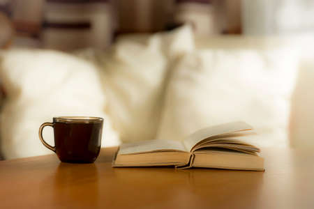 A glass of coffee and a book on the table, on a background of pillows on a light bed