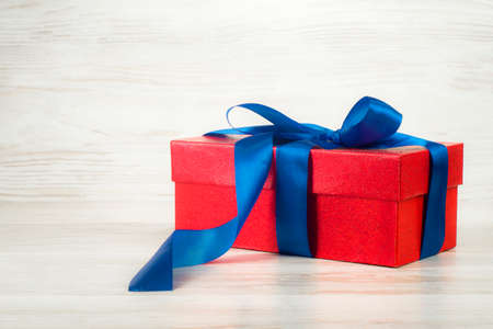 Red gift box - a present, with a blue ribbon on a background of vintage boards