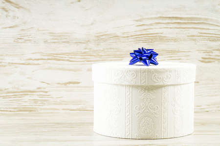 White box with a blue bow on a background of vintage boards