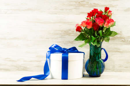 White round box with a blue bow and roses on a background of vintage boards Stockfoto
