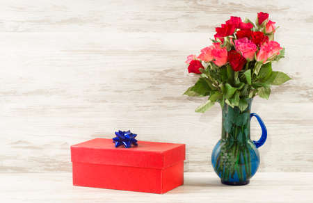 Red gift box - a gift with a blue bow and roses on a background of vintage boards
