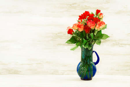 Red roses in a blue vase on a background of bright vintage boards