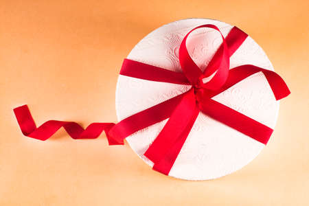 White round box with a red bow, on a colored background