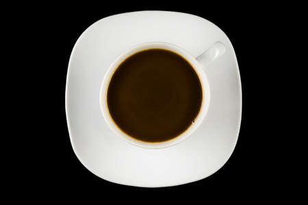 A cup of coffee on a saucer, on a black background - top view