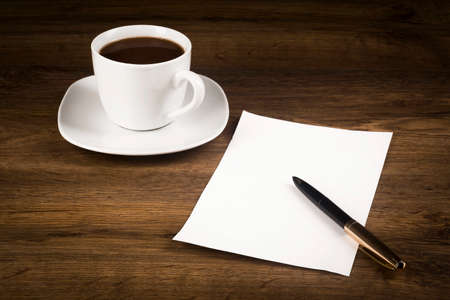 A cup of coffee, a white piece of paper with a pen on the desk top Stockfoto