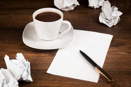 A cup of coffee, a white sheet of paper with a pen, and crumpled sheets of paper on the desk top